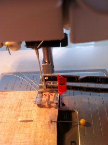 Mesurer avec une règle 1 cm de l'aiguille au bord du tissu.Décaler l'aiguille à gauche jusqu'à l'obtention de 1 cm.Coudre ainsi en suivant le bord du tissu.