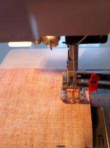 Comment obtenir la distance de 1 cm entre l'aiguille  et le bord du tissu.Utiliser une règle et mesurer la distance de l'aiguille à la ligne sur la plaque à aiguille à droite qui correspondra au cm voulu.