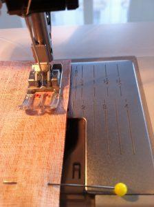 Coudre les 2 tissus à 1 cm de largeur du bord. Bien suivre le repère choisi.Soit la ligne sur la plaque à aiguille.Soit avec le décalage de l'aiguille.