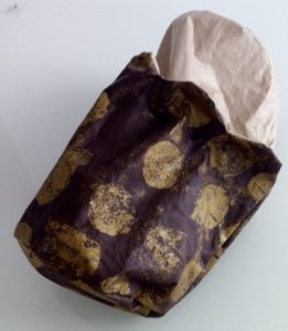 Aller chercher par la fente de 15 cm de la doublure ,l'aumonière marron avec ses pastilles or.