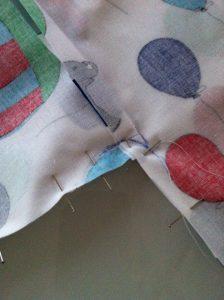 Gros plan de la couture d'assemblage au niveau de l'emmanchure de la blouse de peinture en coton enduit