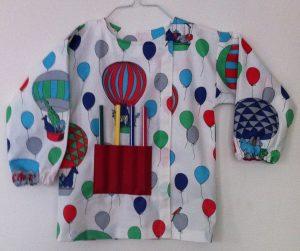 blouse de peinture terminée fermée par un velcro avec  gros crayons dans la poche rouge