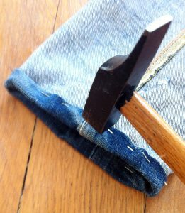 Le marteau qui va aider à coudre l'ourlet du jeans.