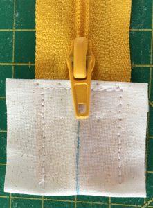 La patte fixée sur le zip.