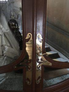 Ferronnerie en cuivre sur la porte de la cage d'escalier.