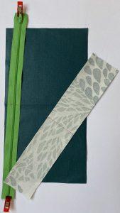 Zip en sandwich entre le tissu vert et la bande a motif