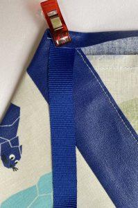 Detail du rabat de la bavette du petit tablier.